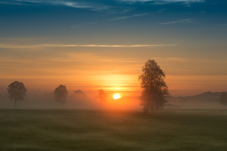 First rays of the sun over foggy field in countryside