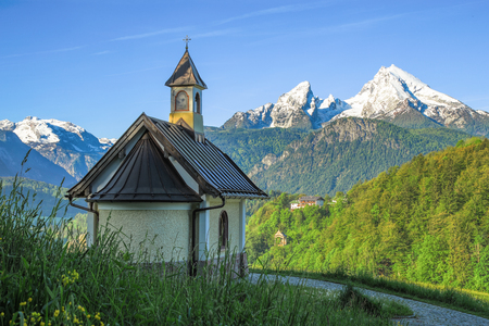 Spring landscape with small chapel and snow-covered Watzmann mountain in Bavarian national park Berchtesgaden Standard-Bild - 97939318