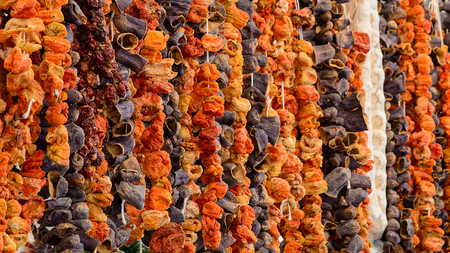 Oriental spices sun dried eggplants paprika peppers and vegetables hanging up at Turkish grocery market Standard-Bild