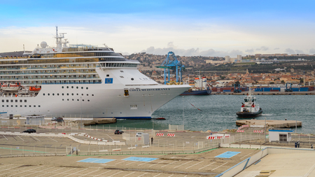 Marseille, France - March 04, 2017: Luxury cruise ship Costa Mediterranea owned by the transport company Costa Crociere entering port of Marseille with tugboat vessel.
