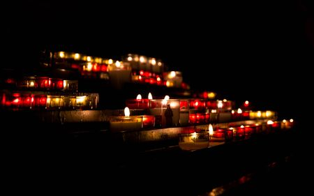Bright lights of burning candles in the darkness of Christian church