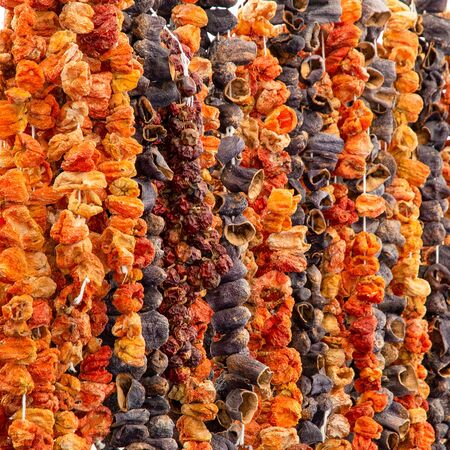 Eastern spices sun dried paprika peppers pods and eggplants fruits hanging at Turkish grocery market