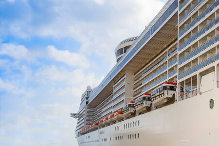 Luxury cruise liner passenger ship with lifeboats for emergency evacuation on the board side view