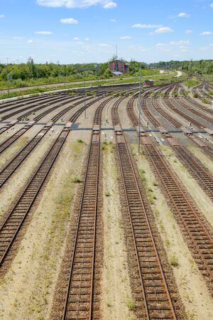 Empty freight railway classification yard with many tracks and operations control tower in the north of Munich. Vertical stock photo.