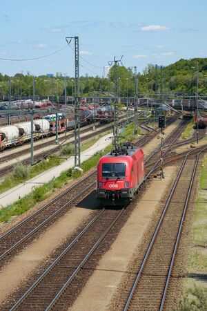 Munich, Germany - July 10, 2019: Red locomotive of Oebb transportation company moving through railroad cargo marshalling station Standard-Bild - 140294147