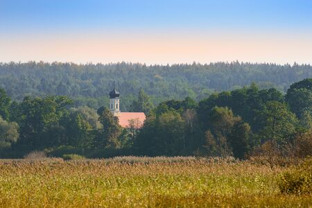 Upper Bavarian autumn landscape with small church in morning mist forest near lake Starnberger See Standard-Bild