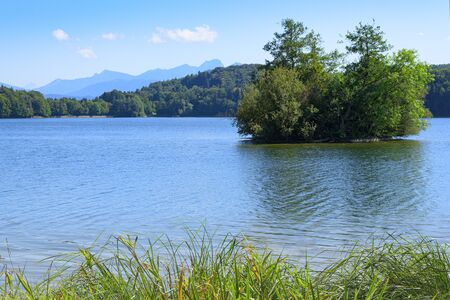 Picturesque view of small lake with wooded islet in Upper Bavaria