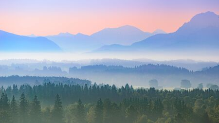 Aerial panoramic landscape of Upper Bavarian foggy foothills with morning sunrise over Alps mountains Standard-Bild