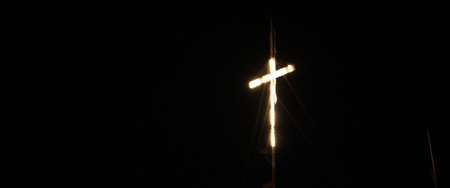 Catholic Cross illuminated at hill Stock Photo