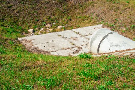 Concrete white rainwater pipe and green grass.