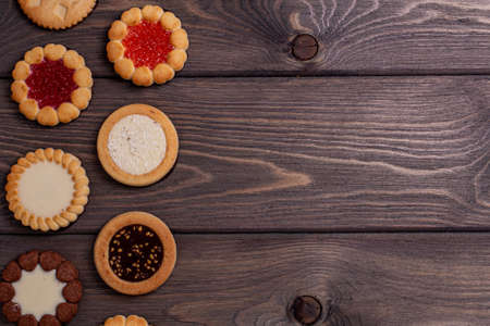 shortbread cookies with various fillings on a brown wooden table. Top view, copy location. Bakery,