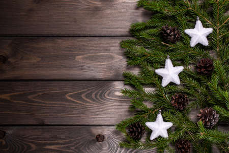 Christmas composition. Christmas white stars and branches of spruce on a brown wooden table. Top view, copy space
