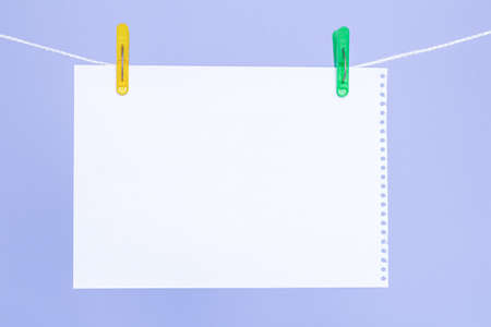 A blank sheet of paper on a clothesline and colored clothespins on a blue background 版權商用圖片