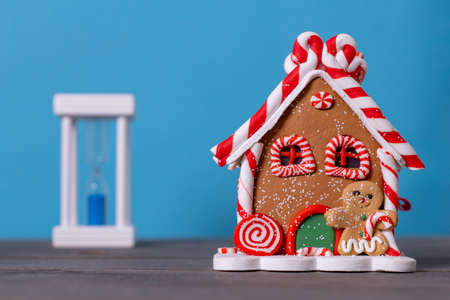 gingerbread house and hourglass on a wooden table on a blue background