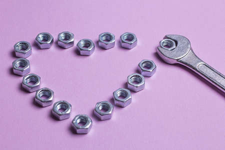 The heart of the nuts with a wrench on a purple paper background. Brutal heart for Valentine's Day