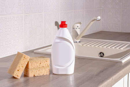 Dish washing liquid with sponges on the kitchen table against the background of the sink