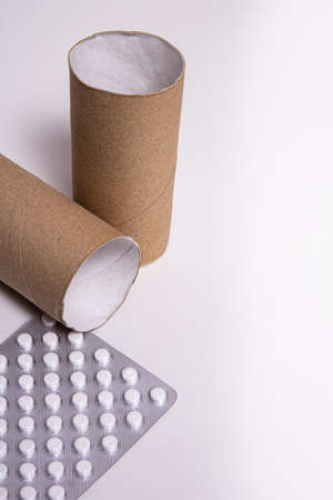 A roll of toilet paper with a package of white pills on a white background. Diarrhea pills