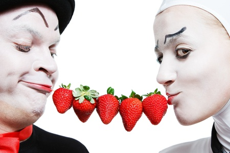 Couple of mimes taking the chain made of strawberries in the mouth and smiling on a white background Stock Photo