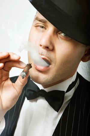 Portret van een man gekleed als een gangster roken sigaar