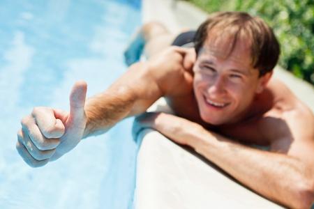 Jonge lachende man zien duim in de buurt van het zwembad Stockfoto