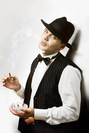 Portrait of a good looking man dressed like a gangster smoking cigar Stock Photo