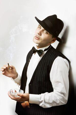 Portret van een goed uitziende man, gekleed als een gangster roken sigaar