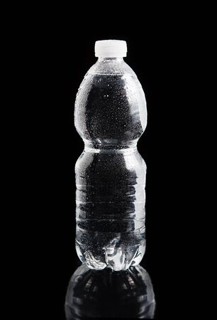 Plastic bottle of water with a drops on it on a black bacground Stock Photo