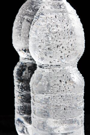 Plastic bottles of water with a drops on it on a black bacground Stock Photo
