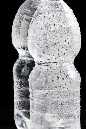 Plastic flessen water met een druppels op het op een zwarte bacground