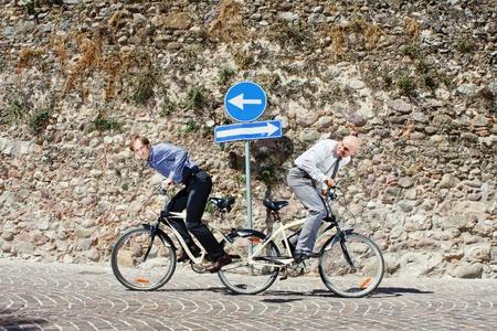 Twee mannen trekken de fiets in hun eigen richting en probeert hard om de wedstrijd te winnen Stockfoto