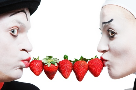 mime: Couple of mimes taking the chain made of strawberries in the mouth and smiling on a white background Stock Photo