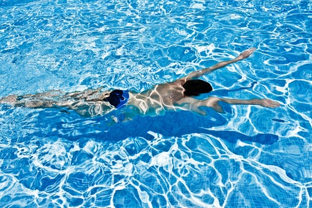 Young man swimming under blue crystal water  in swimming pool photo