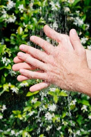 Handen wassen onder vallend water op een kleurrijke groene achtergrond Stockfoto