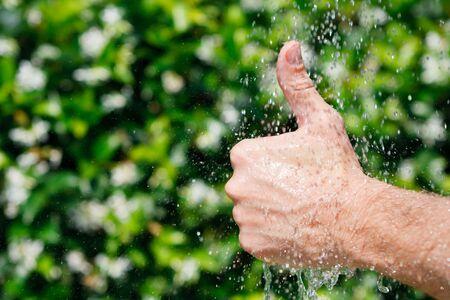 Hand van een man zien duim omhoog op een kleurrijke groene achtergrond Stockfoto