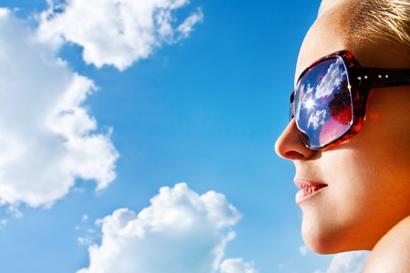 Closeup portrait of a young pretty woman with sunglasses watching the blue  sky with the sun and white clouds