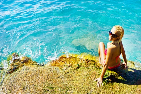 Young attractive woman sitting on the rocks near the blue water of the sea and taking sunbath in a beautiful day of summer