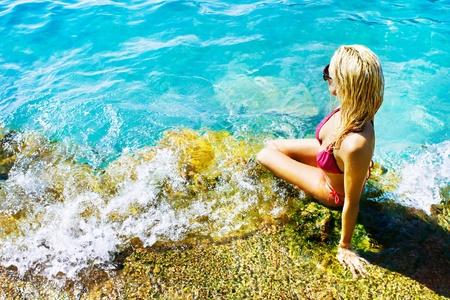 Jonge aantrekkelijke vrouw, zittend op de rotsen bij het blauwe water van de zee en het nemen van zonnebaden op een mooie dag van de zomer