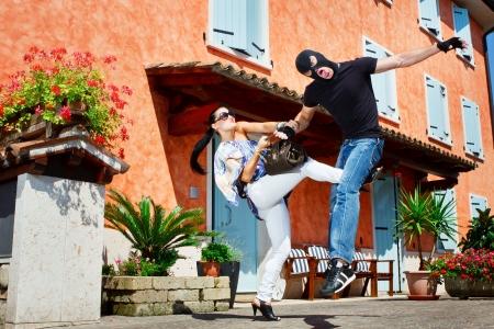 defensa personal: Buena mujer bonita busca defenderse de un atracador patadas entre las piernas, que tratando de robar su bolso en la calle Foto de archivo