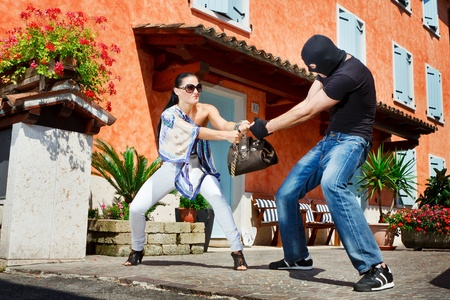 Good looking pretty woman defending herself kicking a mugger between the legs who trying to steal her bag in the street