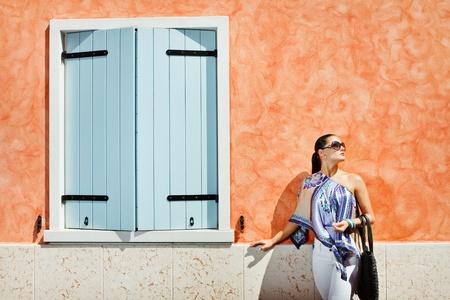 Goed kijken en geklede jonge aantrekkelijke vrouw die zich in de buurt van de oranje muur met een grote blauwe venster