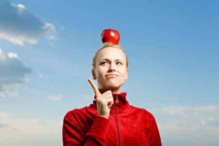 Young attractive woman outdoor holding red apple on her head and thinking about somthing with a blue sky on a background