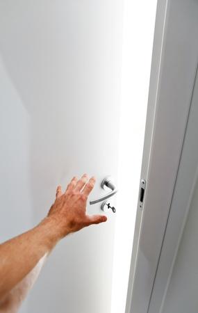 Hand van een man die het openen van witte deur van de donkere naar de kamer vol licht