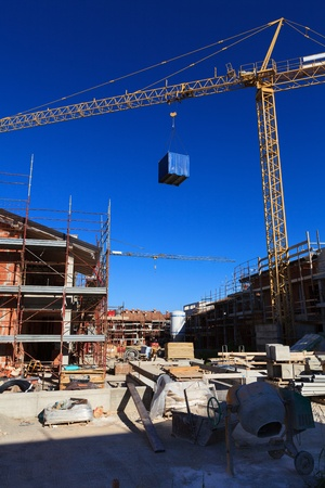 Process of building new houses, sun and blue sky