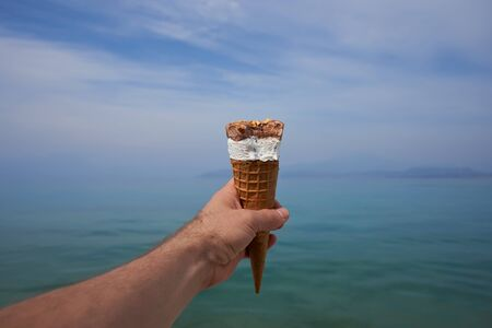 Hand with cone of melting ice cream gelato with a background of blue sky and lake on bright summer day