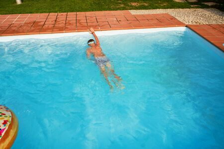 Boy swimming in the open pool in summer