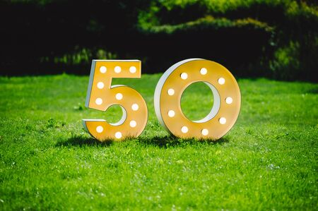 Illuminated decorated number letters symbolising 50th anniversary standing on green field surrounding by dark trees on a sunny day