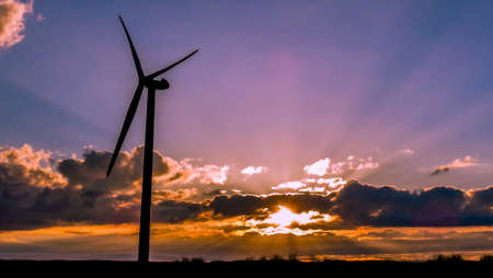 Electrical windmill at colorful sunset generates renewable energy Stock Photo