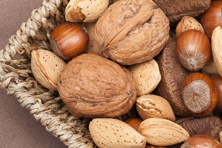 mixed nuts: Basket reach in various kinds of nuts in shells, brazil nuts, almonds, hazelnuts and walnuts.