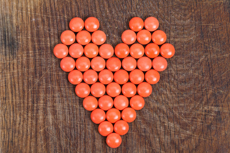 vital: Heart of vitamins, vital heart for Valentines Day on wooden background.