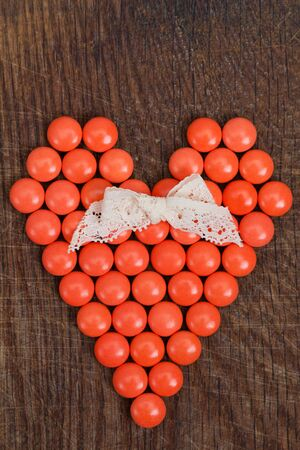 compliment: Heart of vitamins, vital heart for Valentines Day on wooden background.